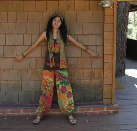 Gigi in harem pants with matching scarf standing at the cabin wall